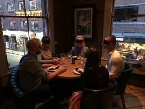 Image of guests blindfolded at a dining table.